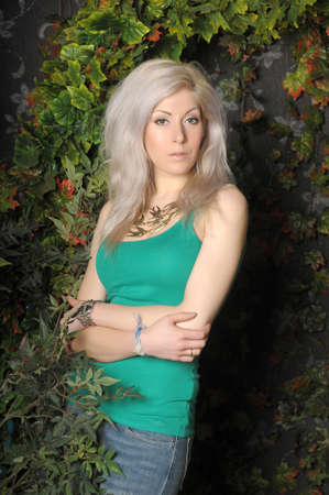 blonde in green with beads on her neck by the tree 免版税图像