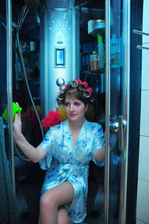 young sexy housewife in curlers washes the shower