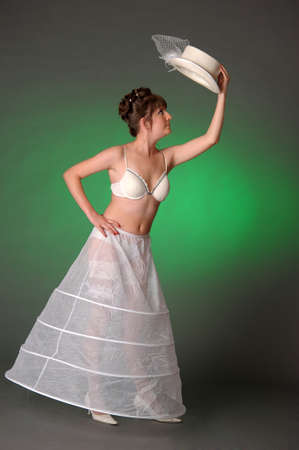 bride in a negligible studio with a hat in her hands 免版税图像
