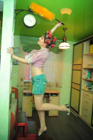 young sexy housewife in curlers wipes dust at home