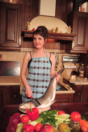 young housewife in the kitchen with a big fish