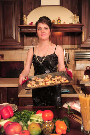 housewife in the kitchen with pastries on a tray