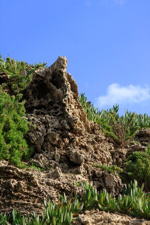 Rock with green grass and blue sky