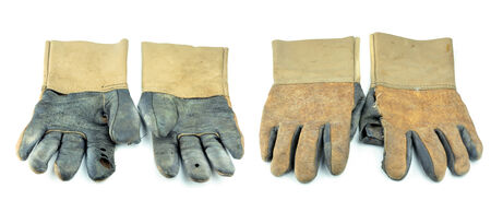 A dirty and well-worn pair of canvas and leather work gloves on white background. photo