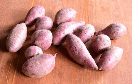 Purple Colored Sweet Potatoes on wood backgrond photo