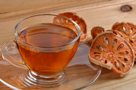 quince: Dried quince and Quince water in glass on wooden table,
