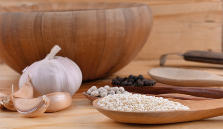 Pepper, sesame seeds with a wooden spoon Stock Photo