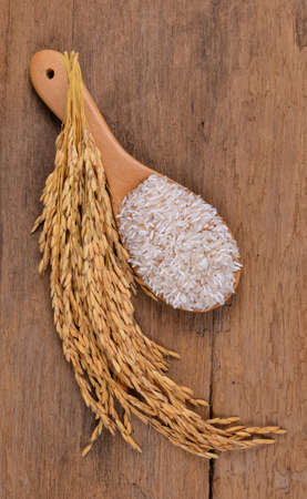 grained: Rice on a wooden spoon on a wooden