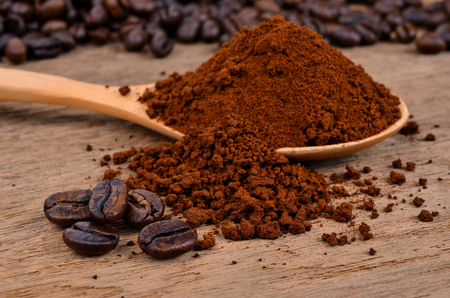 coffee beans and ground coffee on a wooden background 免版税图像