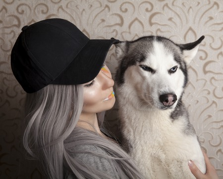 Studio image of a young woman, holding her husky dog, on a background.