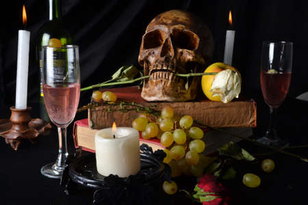 Still life with a skull with roses, books, fruit, wine and candles on a dark background Stockfoto