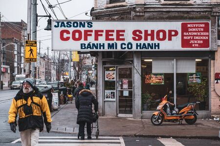 Toronto, ON Canada 12/27/19: Busy street scene of coffee shop and pedestrians on a gritty section of Queen St.