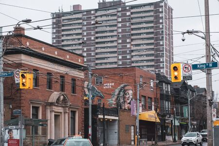 Toronto, ON Canada 12/27/19: Street scene looking into the Parkdale neighbourhood. A bleak apartment building looms overhead. Sajtókép
