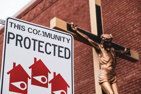 Toronto, ON Canada 12/27/19: Street scene of community watch sign next to crucifix on Roncesvalles Avenue.