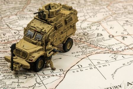 Selective focus of modern military MRAP vehicle on old vintage map from 1902.