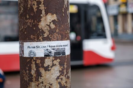 Toronto, ON Canada 12/27/2019:  Anti-poverty sign on rusted electrical pole with a TTC streetcar in the background.