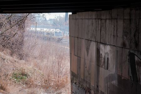Toronto, ON Canada 12/27/2019: Scene of rail tracks heading into Toronto next to graffiti covered underpass. A Union-Pearson airport express train passes by. Sajtókép