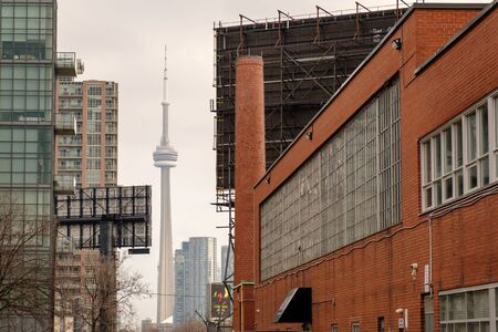 Toronto, ON Canada 12/27/19: Old brick factory next to newer condos in Liberty Village. The CN Tower can be seen looming in the background.