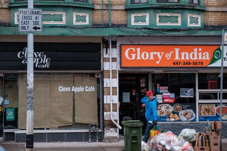 Toronto, ON Canada 12/27/19: Street scene of restaurants on a gritty section of Queen St.