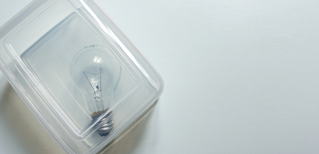 a light bulb placed inside clear box on white wooden surface, think inside the box concept
