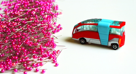 an old bus and a pile of pins on white wooden surface, get into trouble concept
