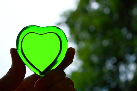 Hand holding green heart made of glass with bokeh background, love or health care concept Imagens