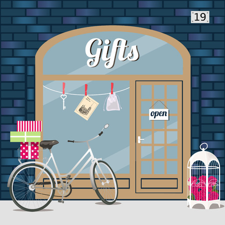 Gifts shops facade of blue brick. Bike with gift boxes in basket and birdcage with roses at the fore . Key, sashe and postcard in the window. Vector illustration eps 10. 向量圖像