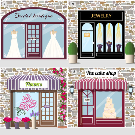 sunblind: Set of wedding shops. Dummies in bridal dresses in the bridal boutique window.Dummies with golden necklaces in the jewelry shop window. Rose sticker on the flower shop window and climbing rose near the door. A big cake in the cake shop window.Building fac