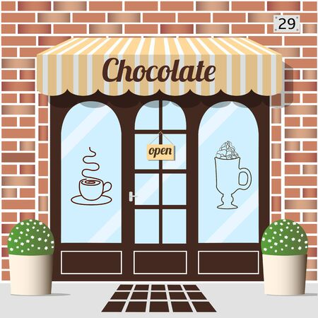 awnings windows: Chocolate shop building. Facade of brick. Chocolate sign sticker on window.