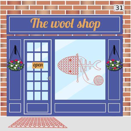 Lana negozio edificio. Facciata di mattoni rossi. Knitting adesivo segno sulla finestra.