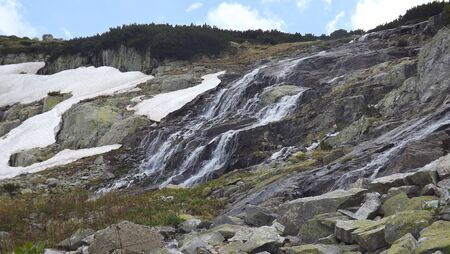 defrost: Defrosted snow which flows down gently on the rocks of the mountain. On the other side there is snow.
