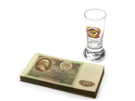 Stack of Soviet 1961 fifty rubles and a vodka glass with USSR national emblem isolated on a white background.
