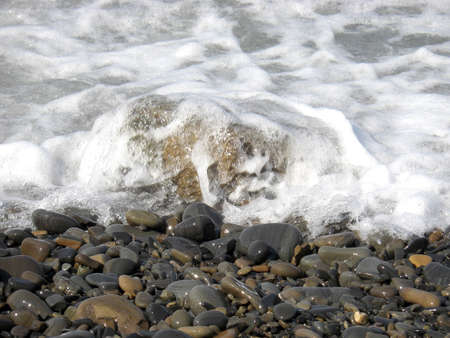 Background from beach pebbles and sea foam. Stock Photo