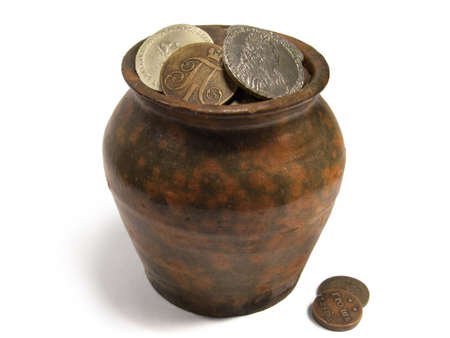 Aged jug with very old silver and copper coins isolated on white background.