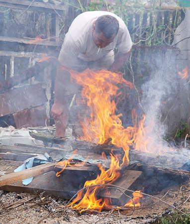 residuos toxicos: Fumar causa de la llama de fuego tóxicos y el hombre tratando de apagar el fuego