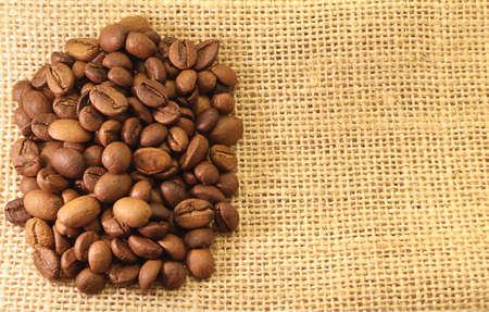Koffiebonen op materiaal geweven achtergrond Stockfoto - 13794234