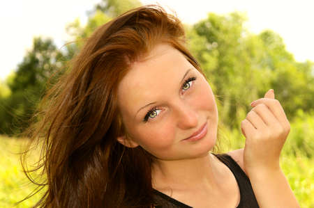 Woman Face smiling with thick Brown Hair on wind beautiful Outdoor with nature on background
