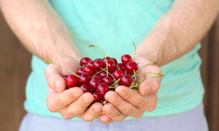 Cherry Berries in Man Hands natural organic fresh product with water drops