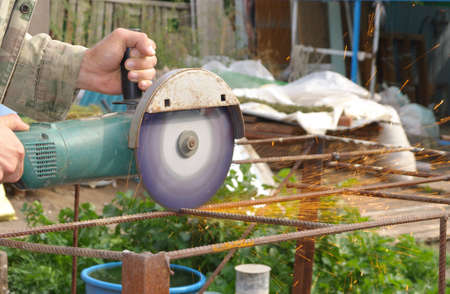 Angle Grinder Metal sawing with flashing sparks close up and Repairman hands home repair garden working summer time  Also called Circular Saw handheld electric instrument
