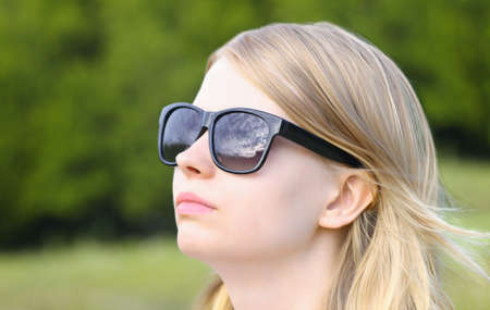 Woman wearing Sunglasses with sky mirroring Blond Hair Head Look up Outdoor Summer Day Stock Photo