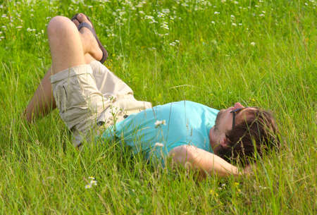 Man laying on grass field Summer day Relaxation Outdoor Leisure Time on Nature Stock Photo