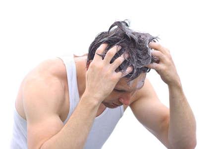 Giovane uomo di lavaggio testa capelli con shampoo schiuma isolato su sfondo bianco