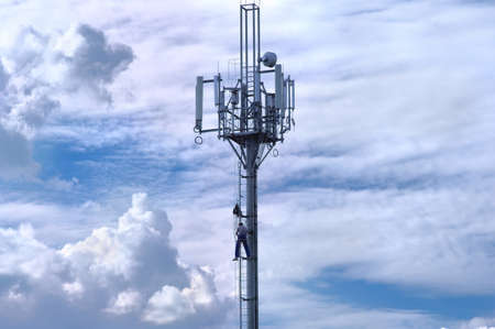 Repairman on Telecommunications tower with antenna Sky Clouds on background photo