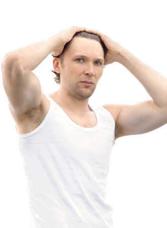 Young Man upsweeping Hair with his muscular arms raised on his Head isolated on white background Stock Photo