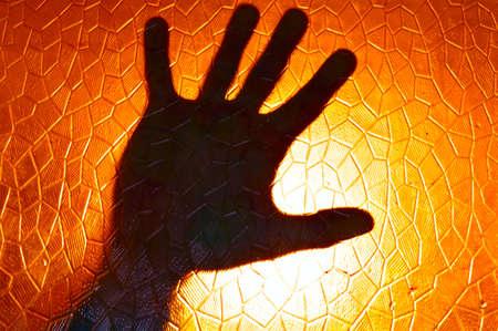 ホラー映画のような幾何学的パターンと恐怖症とうつ病の感情の概念と火のオレンジ色の背景のステンド グラスにシルエットを手します。 写真素材