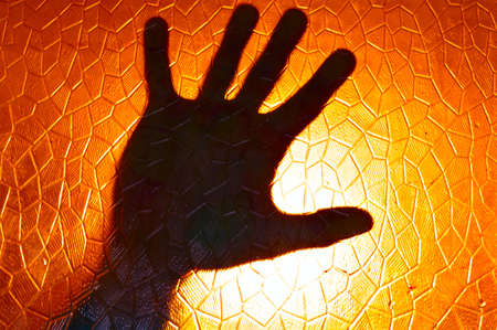 Hand Silhouette on Fire Orange Color Background stained glass with geometric pattern Horror Cinematic and concept of Phobia and Depression Emotion Stock Photo
