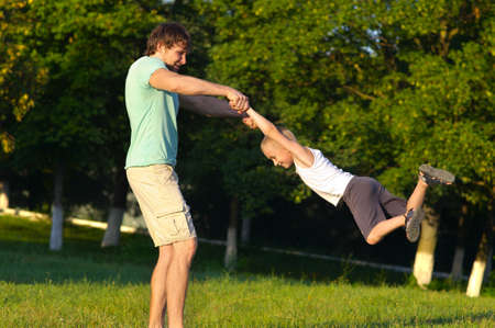 Familia Padre Hombre y del hijo del muchacho que juega el parque al aire libre volar emoción felicidad redonda con la naturaleza del verano en el fondo