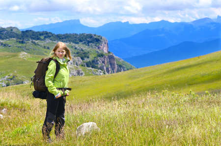 Woman Hiker with Backpack standing Outdoor on green Valley Grass and Mountains rocks on background Summer Day photo