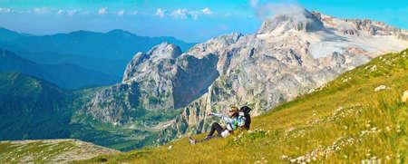Mulher pedestrianismo viajante nas montanhas que relaxa na grama com a mochila picos rochosos no fundo