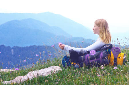 Woman Traveller with backpack sitting on grass with flowers relaxing with Mountains on Background